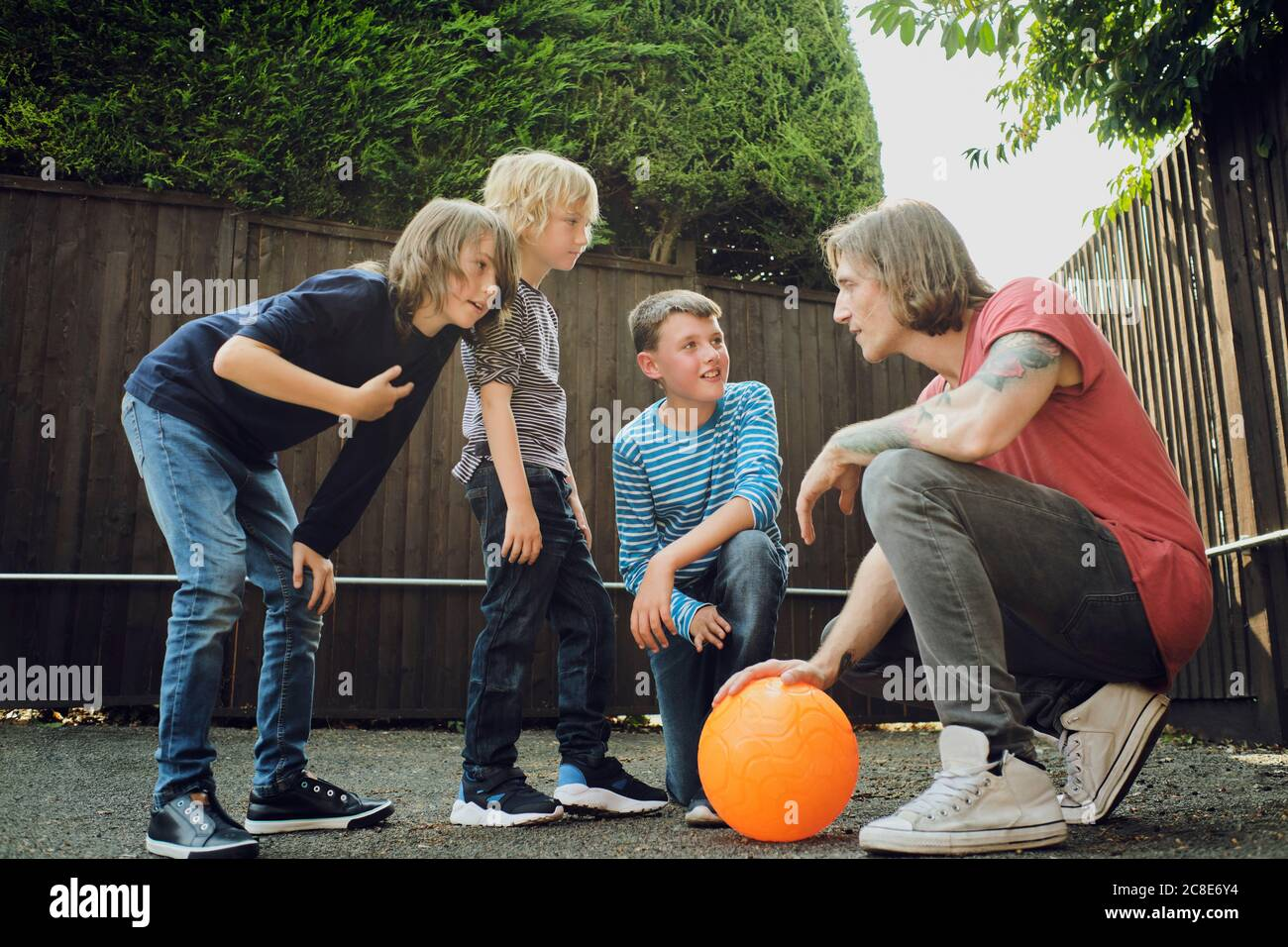 Man and boys discussing strategy over basketball at yard Stock Photo