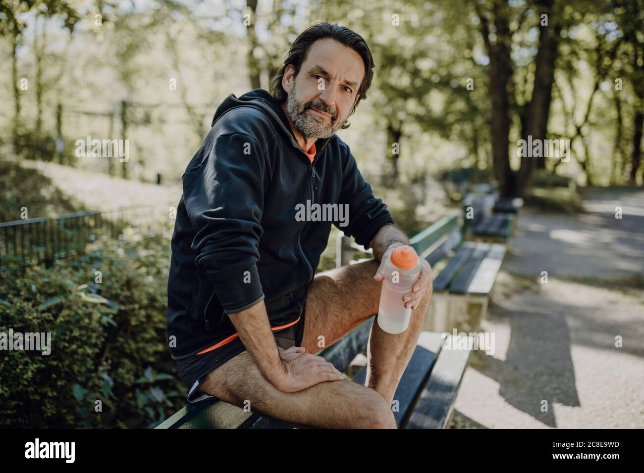 Confident mature man holding water bottle while sitting on bench in park Stock Photo