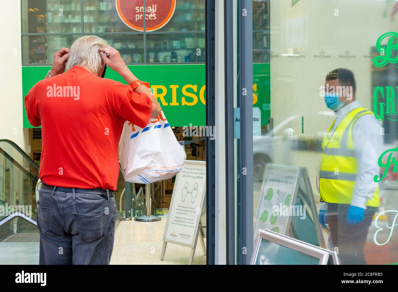 London Uk Friday 24 July 2020 A Shopper Putting On A Protective Mask On Entering A