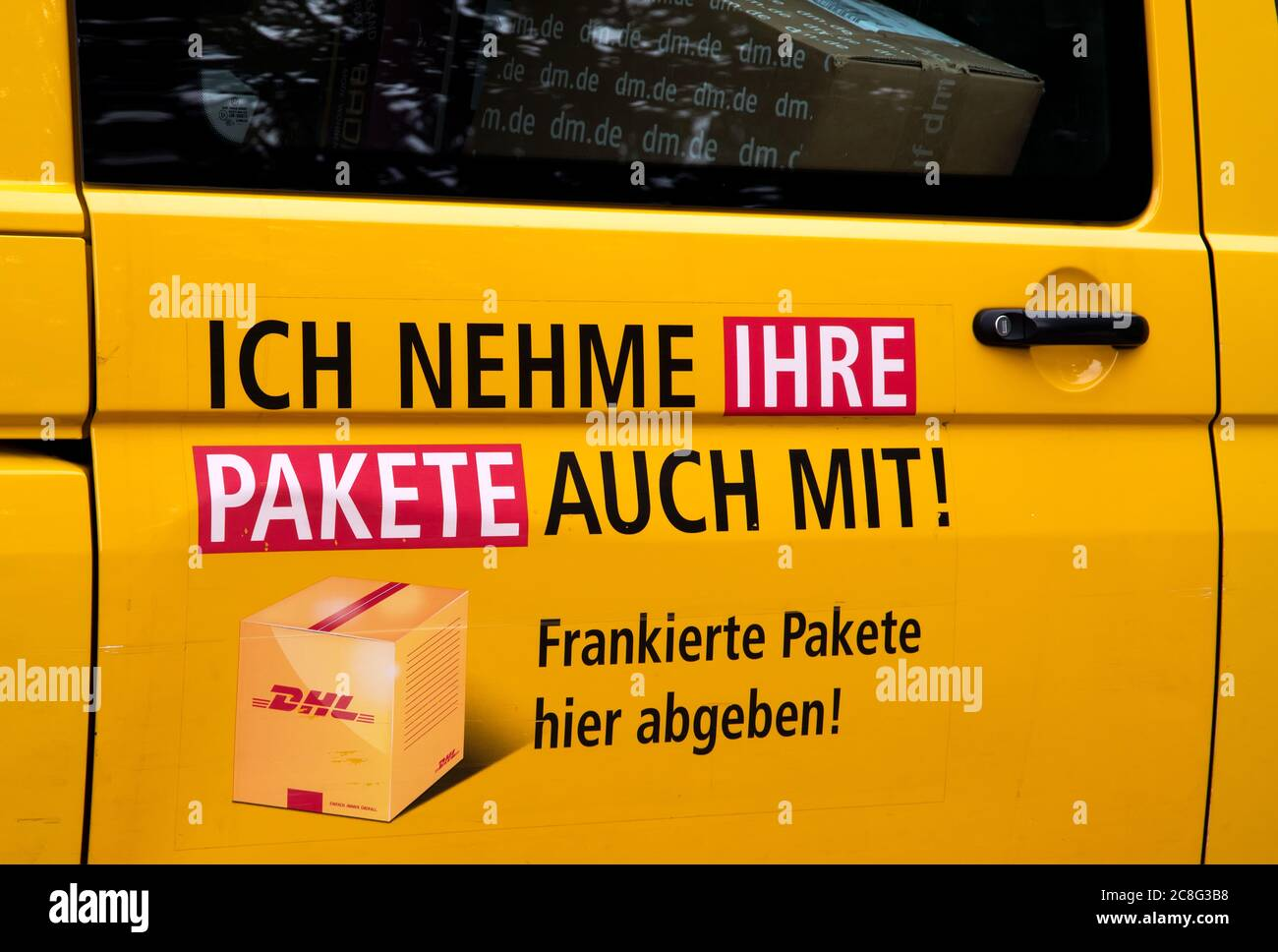 Door of a DHL transporter with the indication that parcels are being taken along. (Ich nehme auch ihre Pakete mit) Stock Photo