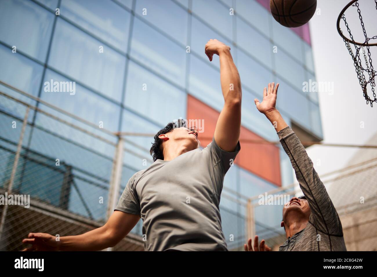 two young asian men playing basketball going up for a rebound on outdoor court Stock Photo