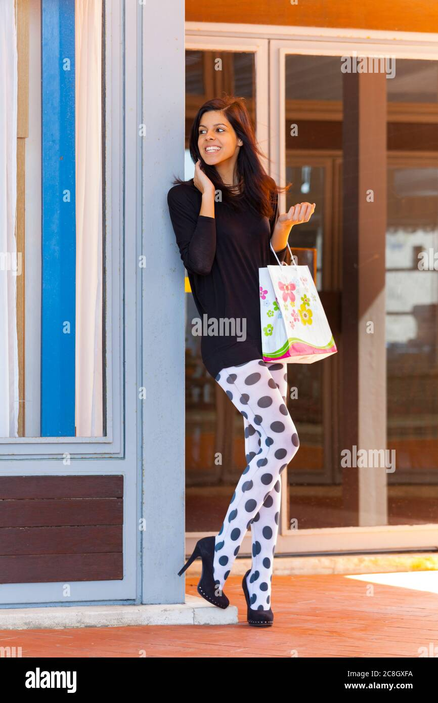 Shopper teengirl with paper shopping bag holding hold hand hands happily looking away aside anxiously waiting presumably friend smiling heelsaddict Stock Photo