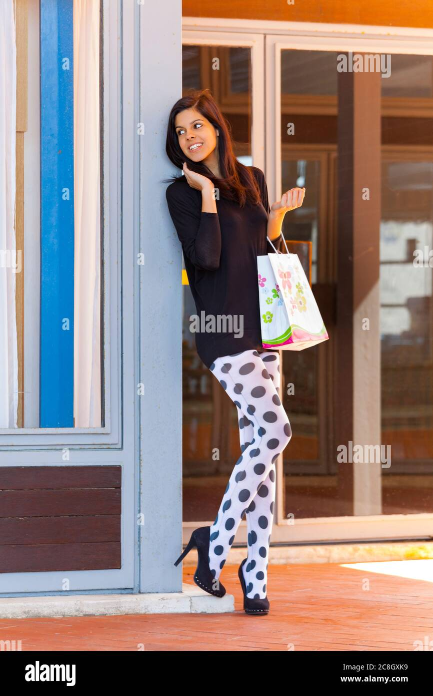 Shopper teengirl with shopping bag holding hold hand hands happily looking aside anxiously waiting somebody presumably friend smiling heelsaddicted Stock Photo
