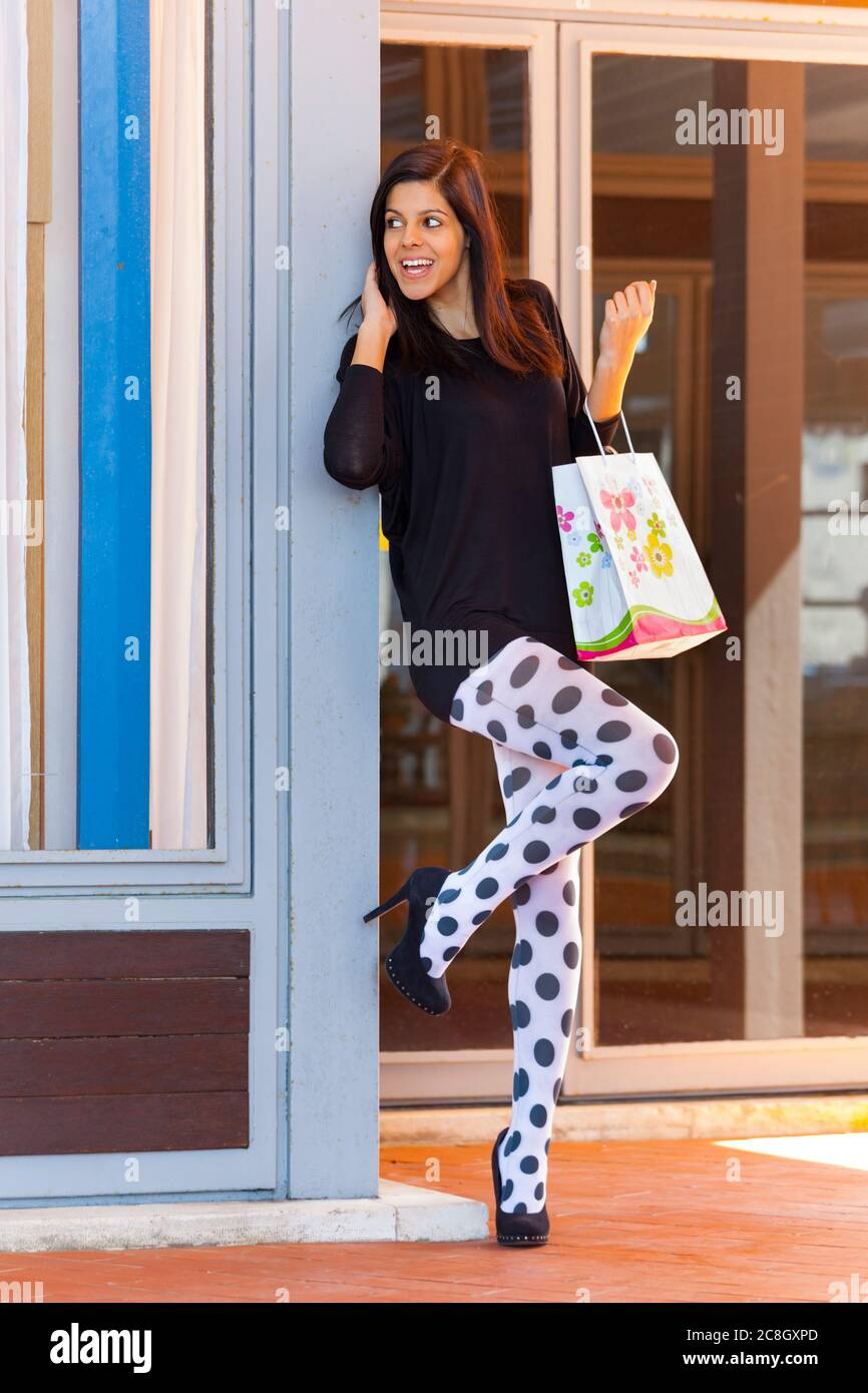 Shopper teengirl with paper shopping bag holding hold hand hands happily looking away aside anxiously waiting dor somebody presumably friend laughing Stock Photo