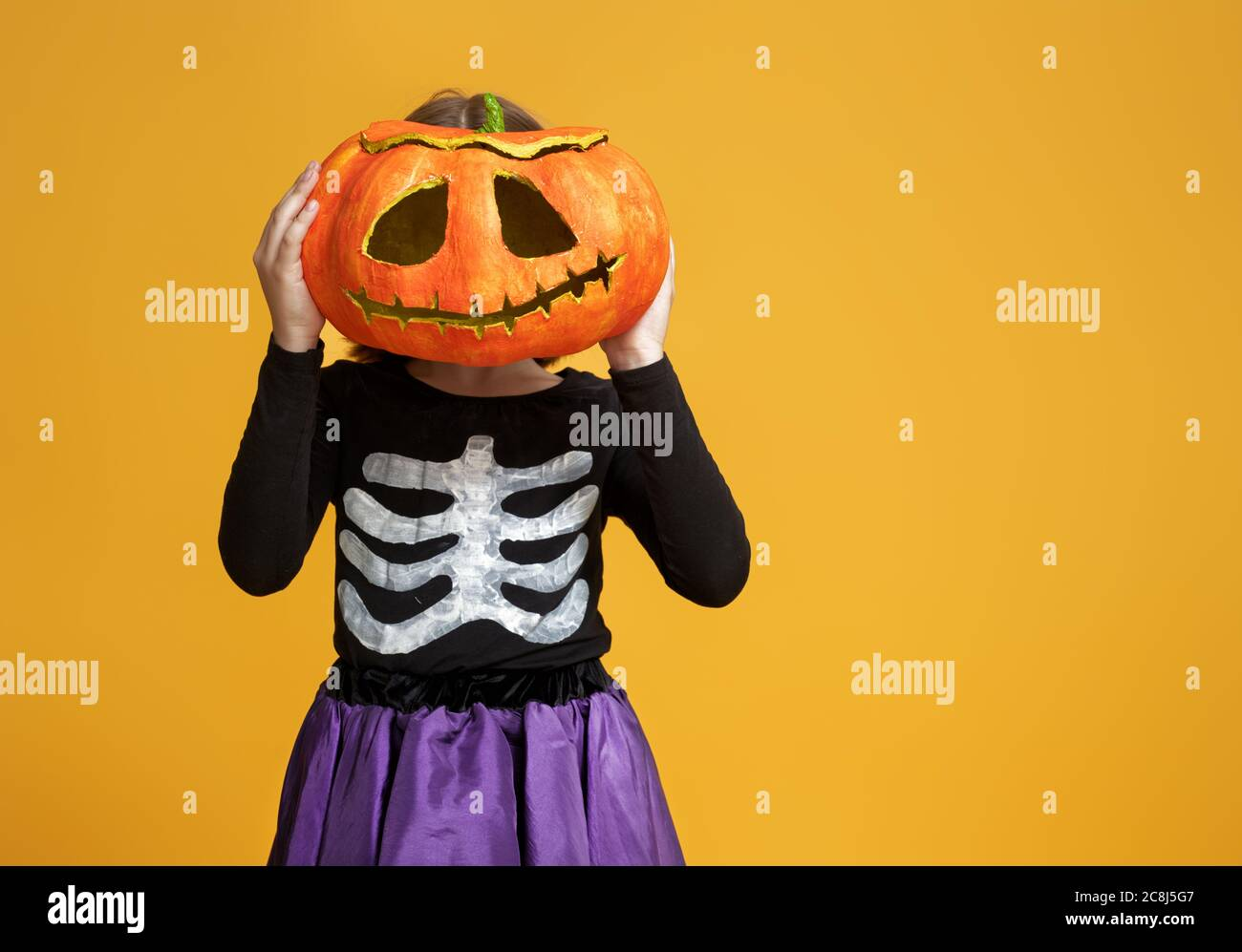 Happy Halloween Cute Little Girl In Skeleton Costume With Pumpkin On Yellow Background Stock Photo Alamy