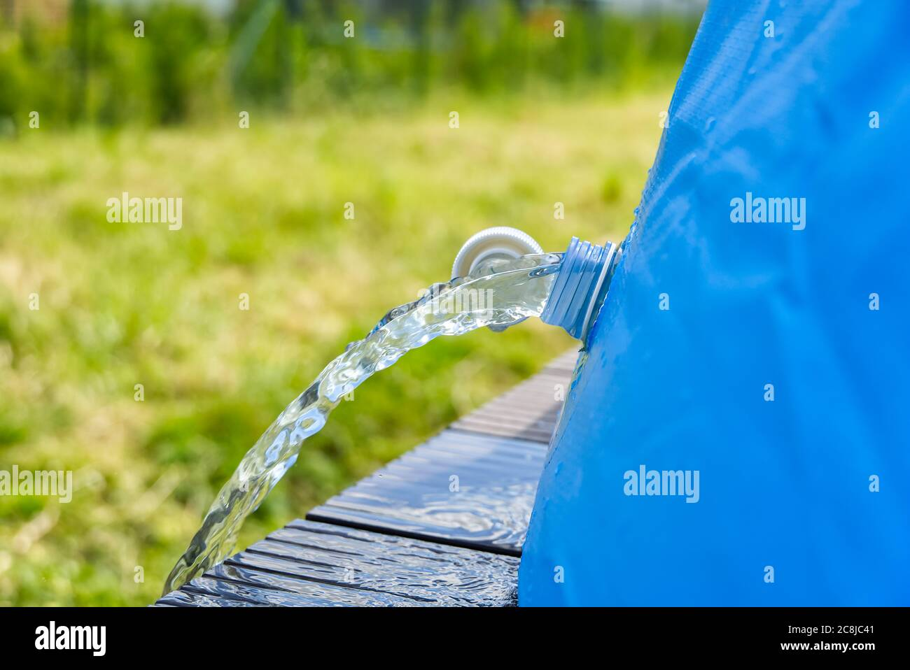 Drainage of water from an outdoor inflatable swimming pool. inflatable swimming pool care concept. Stock Photo