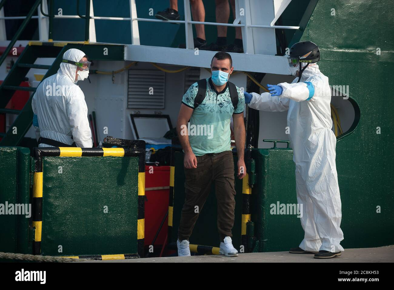 Members of European Border and Coast Guard Agency (Frontex) help a migrant to disembark from a patrol vessel at Malaga port after being intercepted by Spanish Civil Guards authorities on the Mediterranean Sea.A Spanish Civil Guard vessel intercepted around 82 Algerian migrants near Almeria's coast while trying to reach Europe by small boats. During the coronavirus pandemic, the closure of Morocco's border with Spain as a measure to prevent the spread of coronavirus disease has caused a drastic drop in the number of migrants that try to reach the Spanish coasts across Alboran Sea route, while t Stock Photo