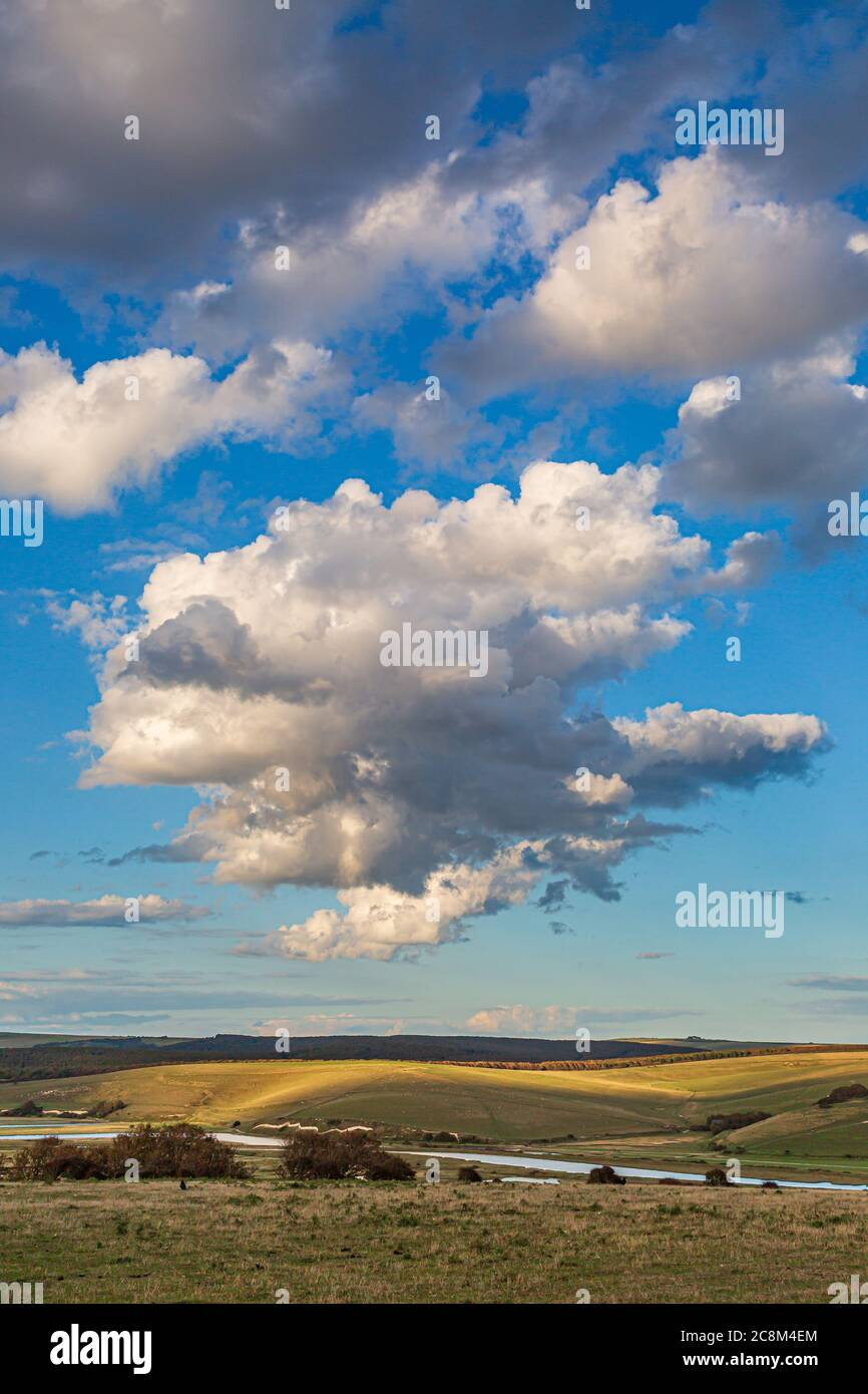 Fluffy clouds over the Cuckmere River in South Downs in Sussex, on a sunny summers evening Stock Photo