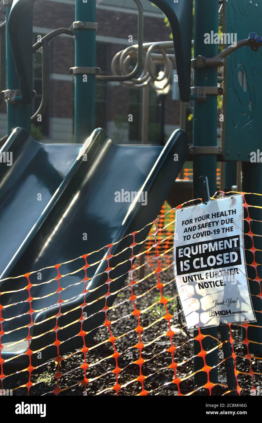 A sign and plastic orange fencing around a children's playground,sign saying 'Equipment is Closed until Further Notice', due to COVID-19 pandemic Stock Photo