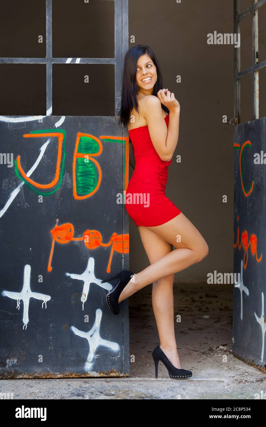 Legs minidress and heels female teen  is looking back away aside over her shoulder teasingly seductively balancing raising raise leg smiling smile Stock Photo