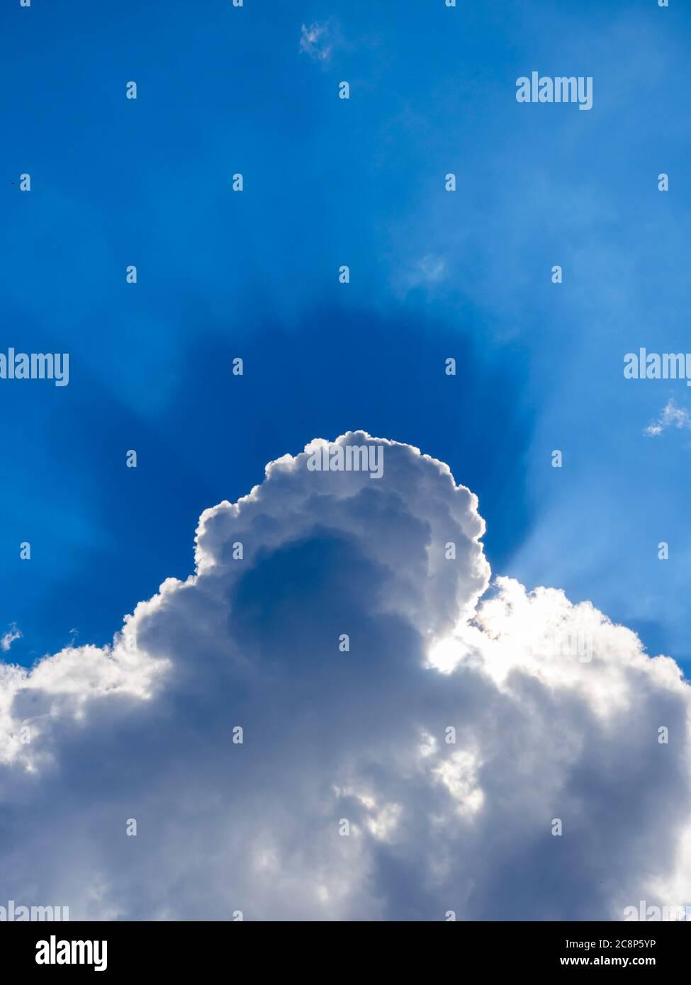 Dark Blue sun rays sunrays near behind White clouds cloud view against sky sunshine sunlight sunny Stock Photo
