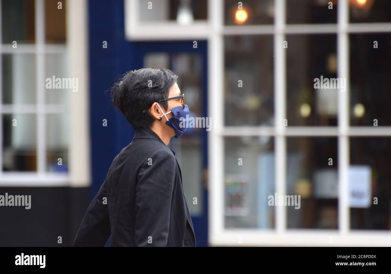 A woman walks along the street in England following a law being passed making wearing face coverings compulsory in Retail Settings on July 24 2020 Stock Photo