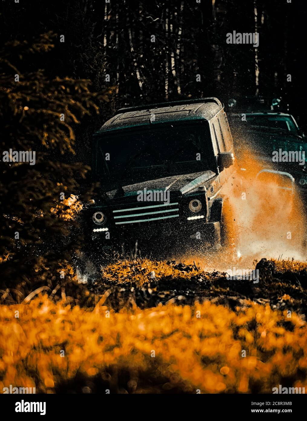 Mud and water splash in off-road racing. Drag racing car burns rubber. Extreme. Off-road car. Expedition offroader. Mudding is off-roading through an Stock Photo
