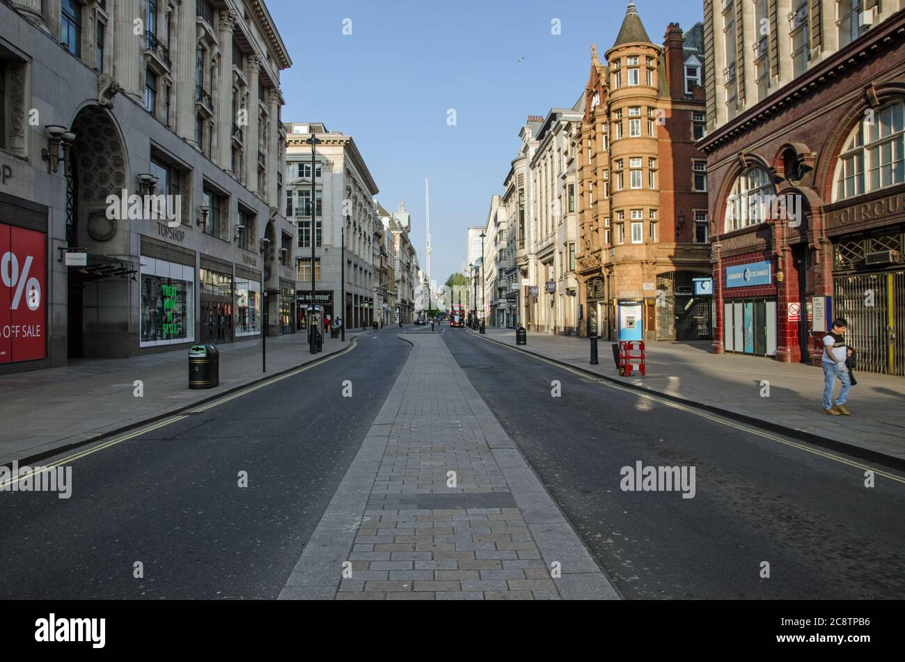 London, UK - April 24, 2020: An almost deserted Oxford Street on a sunny Spring afternoon during the COVID19 lockdown.  Only a few pedestrians and veh Stock Photo