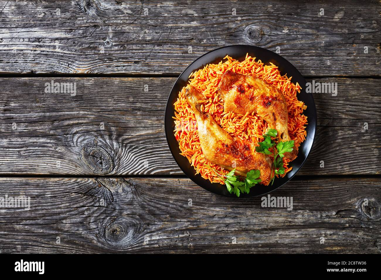 South Indian Tomato Rice Cooked With Sauteed Tomatoes Onion Red Chili Powder Cinnamon Turmeric With Oven Baked Chicken Quarters On A Black Plate Stock Photo Alamy