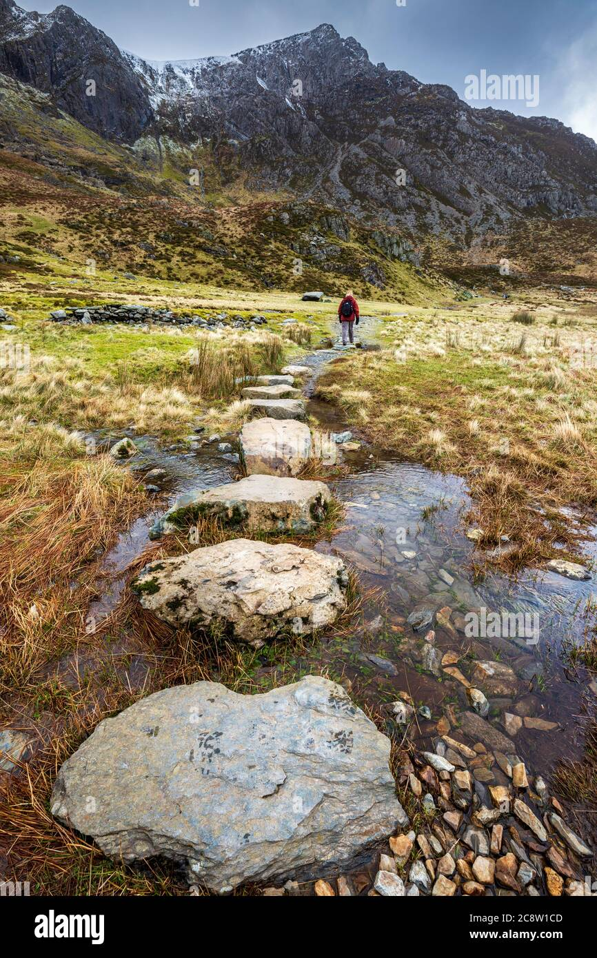 Stepping stones across melt water from the snow covered mountains of Glyder Fawr leading to Llyn Idwal, Snowdonia National Park, North Wales Stock Photo