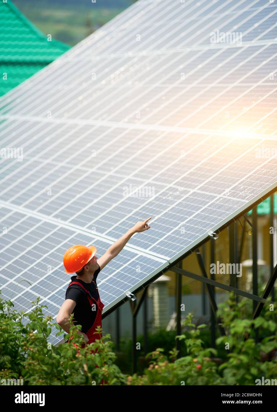 Man worker in an orange helmet pointing at a high solar station on a plot of land with greenery. Alternative cheap sun energy production and profitable financial investment concept Stock Photo