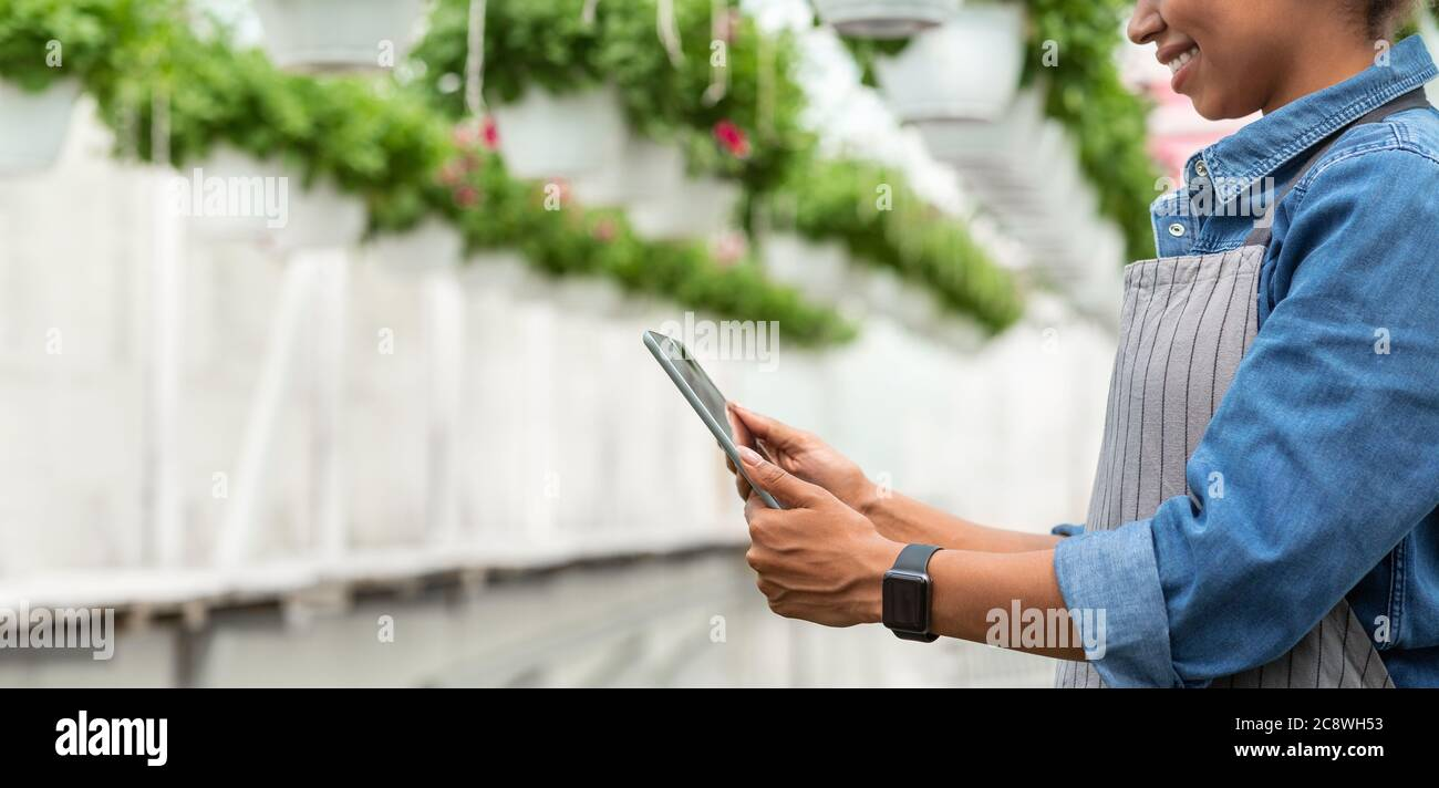 Modern devices for work in greenhouse. Smiling girl with tablet working in greenhouse Stock Photo