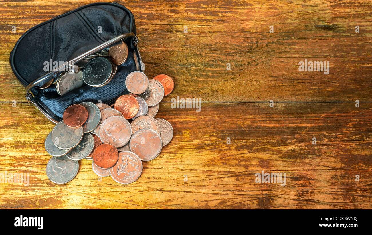 Open black leather pocket wallet full of various coins. Financial crisis, poverty, lack of money. On wooden background or table. Flat lay. Top view. C Stock Photo
