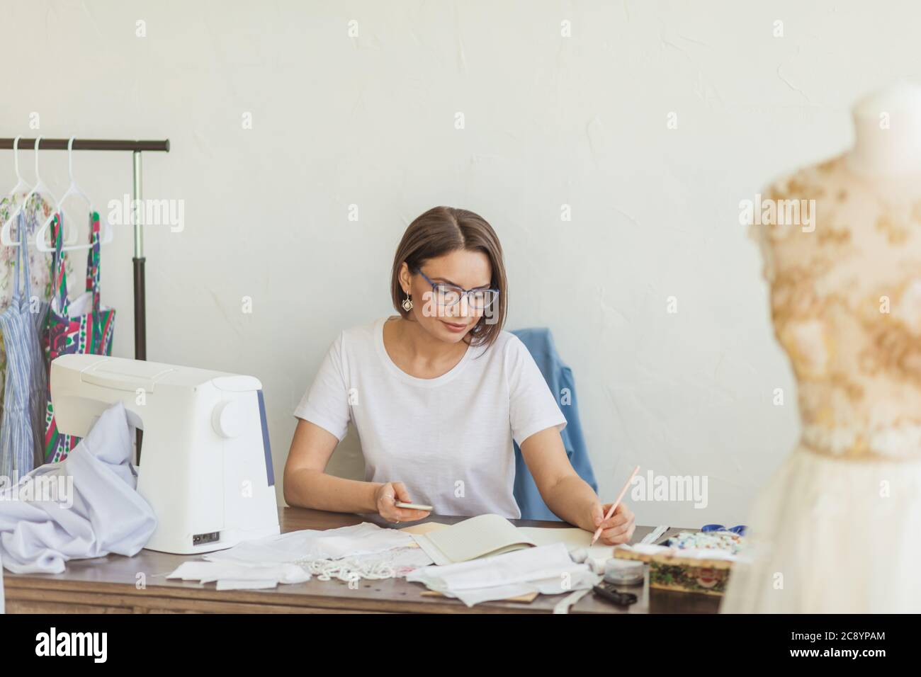 Young Caucasian Female Dress Designer In Casual Wear Is Drawing Sketches Of New Men And Women S Apparel Summer Collection Stock Photo Alamy