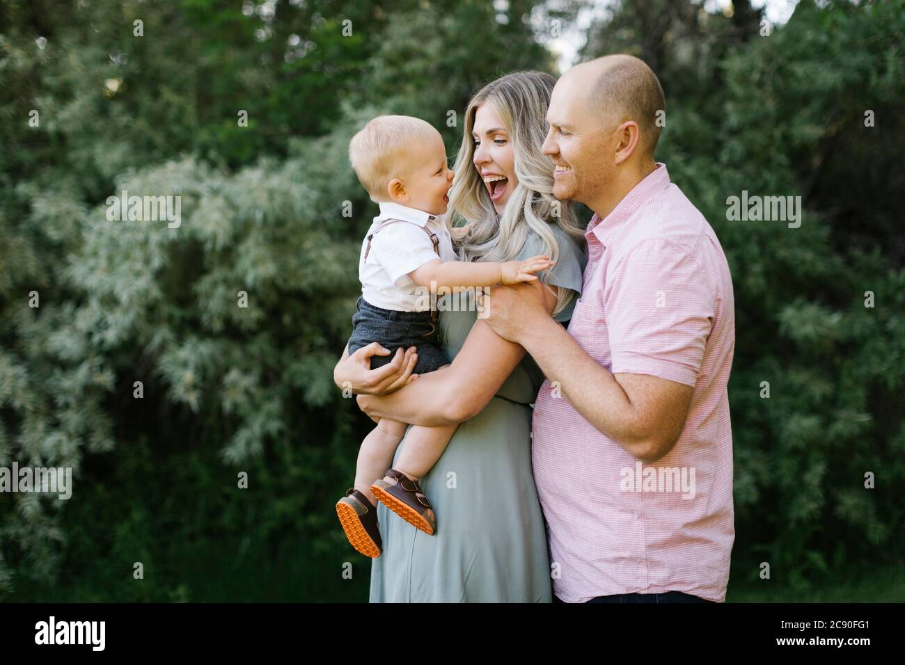 Parents embracing with baby son outdoors Stock Photo