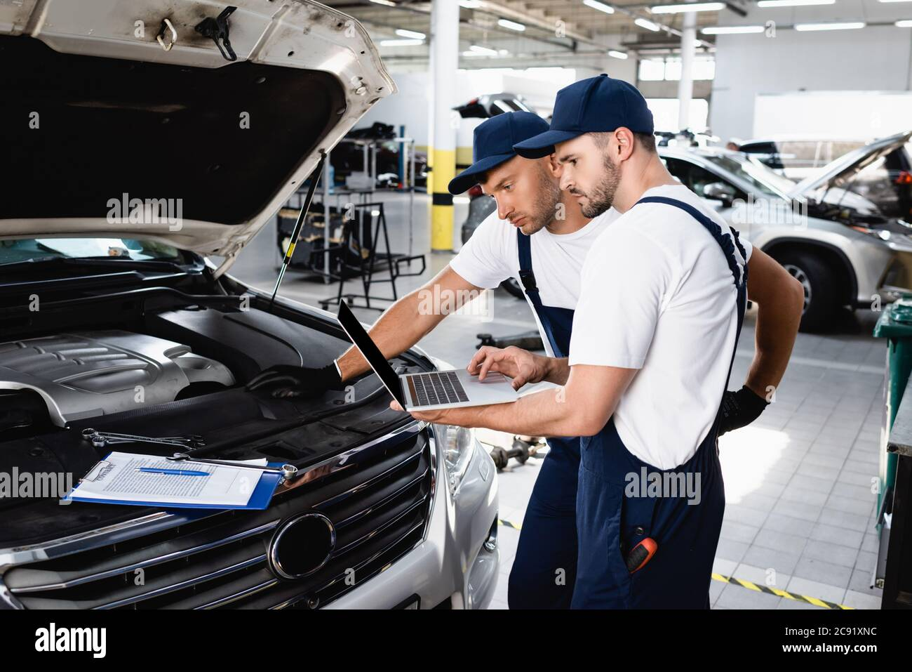 Auto Mechanics Looking At Laptop Screen Near Open Hood Of Car At Service Station Stock Photo Alamy