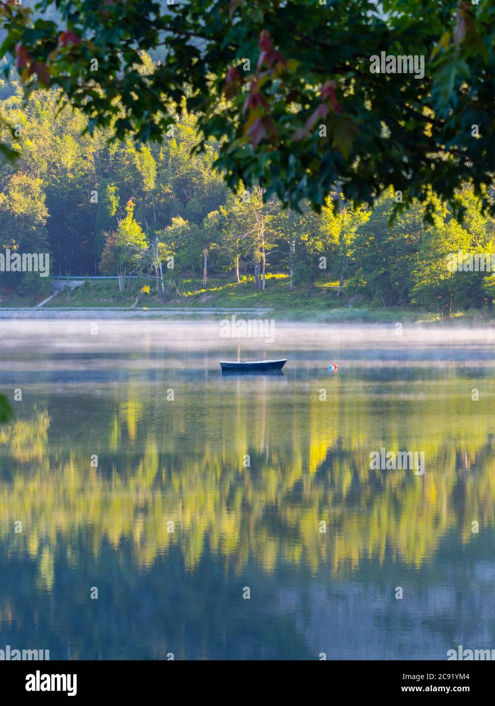 Lonesome boat on lake Bajer in Fuzine Croatia Europe fog mist vapour floating float just about water surface gorgeous & stunning & marvelous Stock Photo