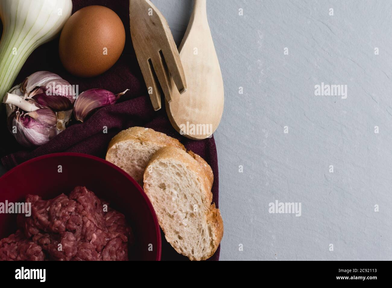 Closeup shot of ingredients and tools for preparing meatballs on a white kitchen table Stock Photo