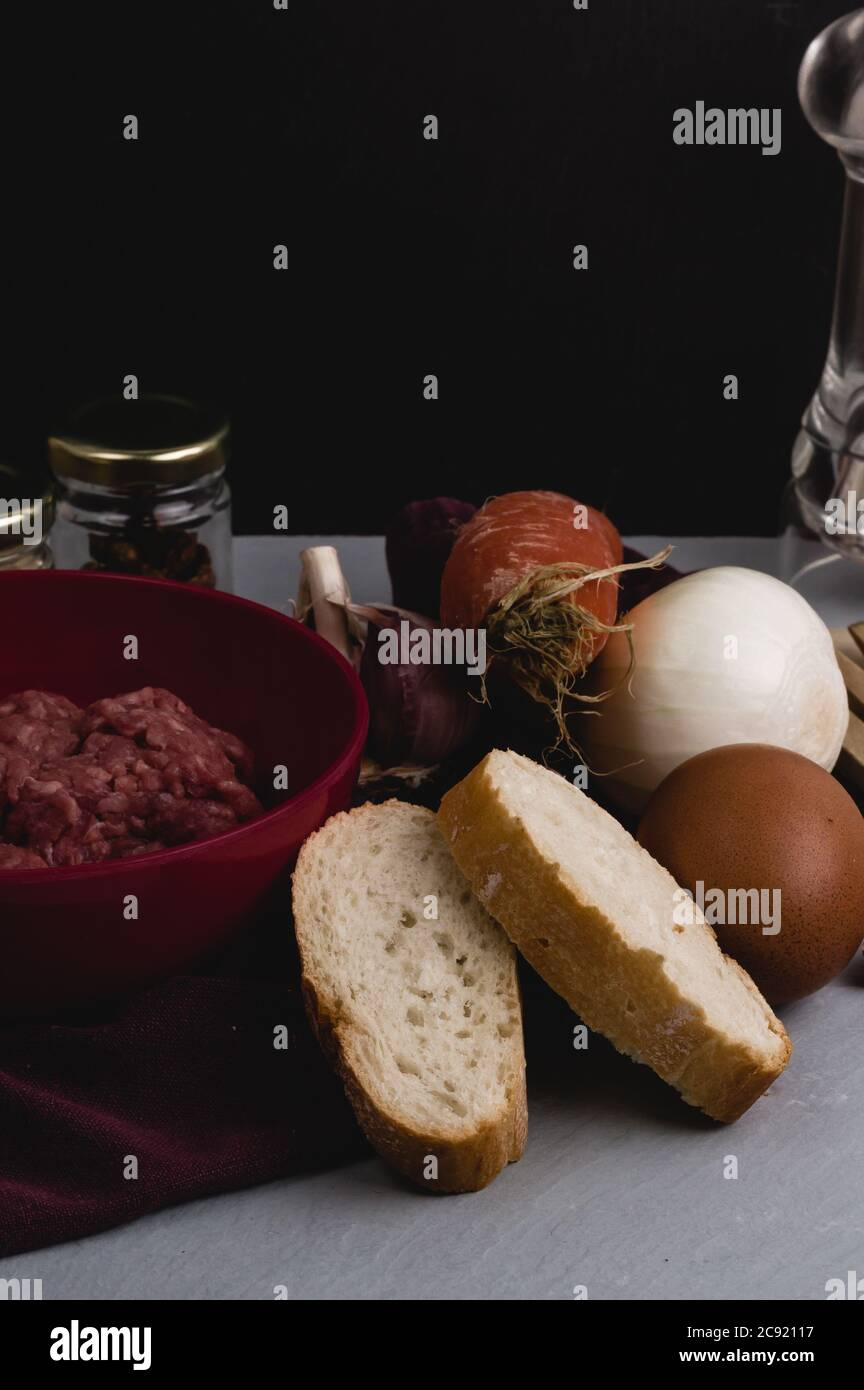 Vertical closeup shot of ingredients for preparing meatballs on a white kitchen table Stock Photo