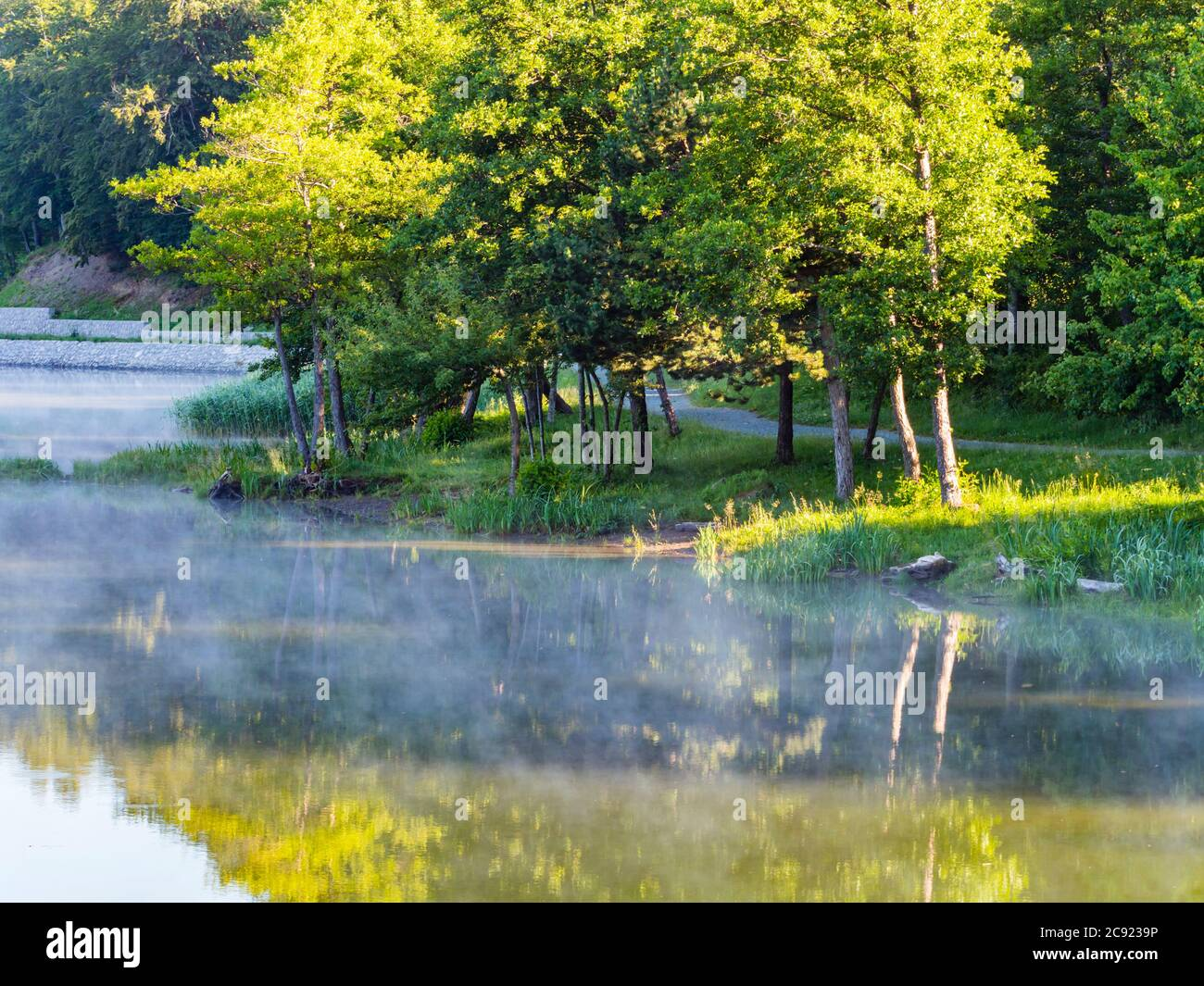 Promenade on Lake Bajer in Fuzine Croatia Europe fog mist vapour floating float just about water surface Stock Photo