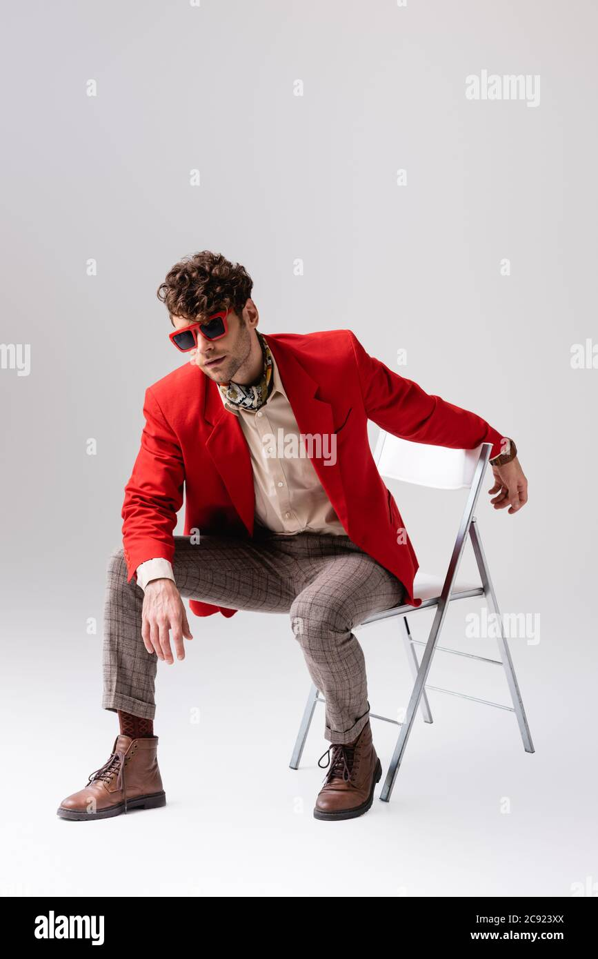Stylish Man In Red Blazer Leaning Forward And Posing While Sitting On Chair On Grey Stock Photo Alamy
