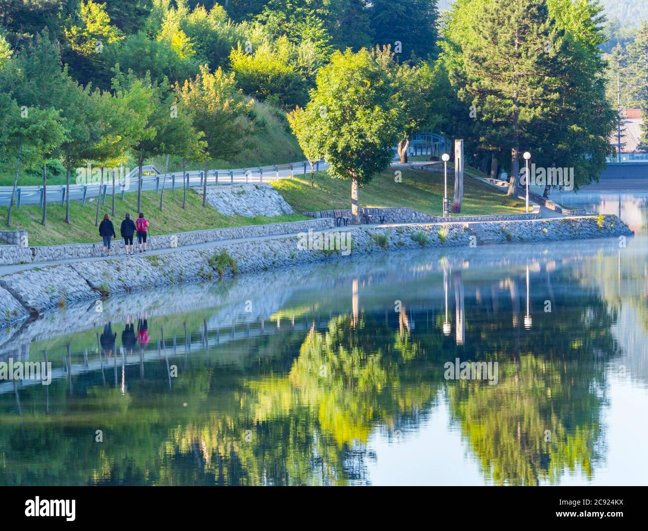 Morning joggers on coastline promenade on lake Bajer in Fuzine Croatia Europe Stock Photo