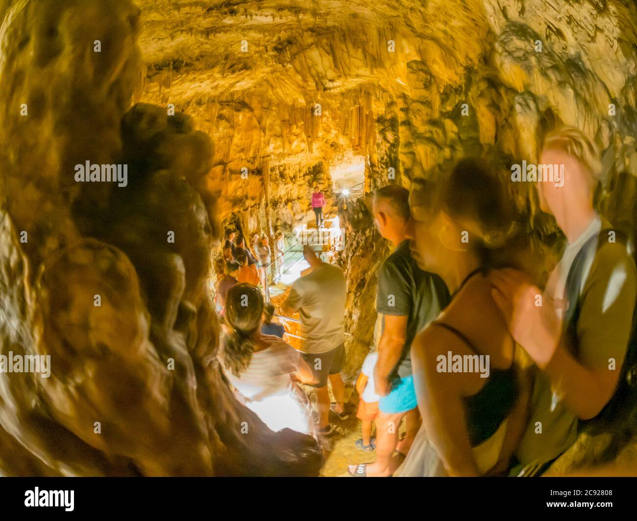 Busy cave Biserujka in island Krk in Croatia Europe with numerous visitors tourists standing listen listening to guide Stock Photo