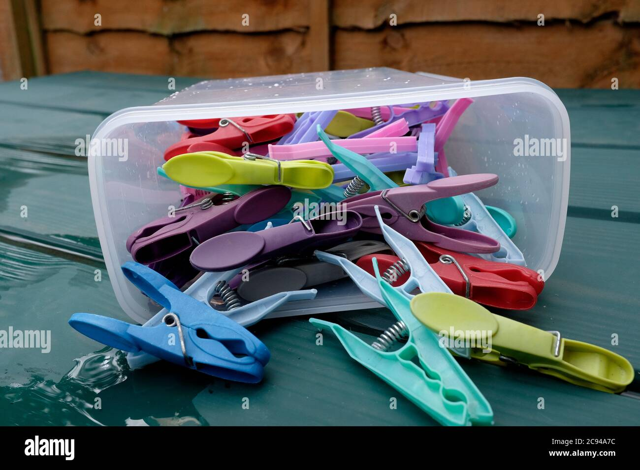 coloured plastic washing line pegs in a plastic peg box displayed in a exterior setting sturry east kent uk july 2020 Stock Photo