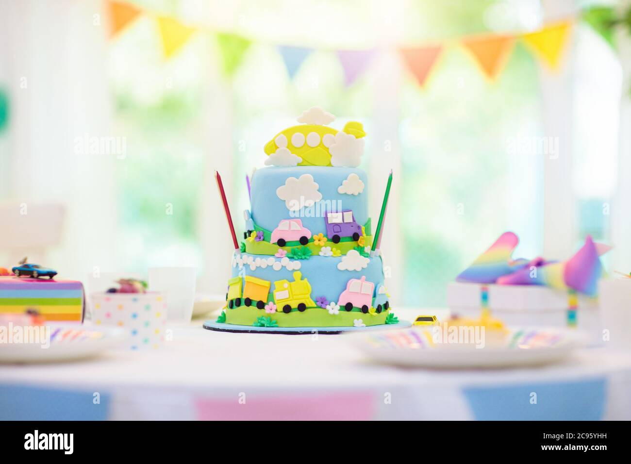 Kids Birthday Party Boy Cake With Car And Airplane Child Blowing Out Candles On Colorful Cake Party Decorations Rainbow Flag Banners Balloons Ve Stock Photo Alamy