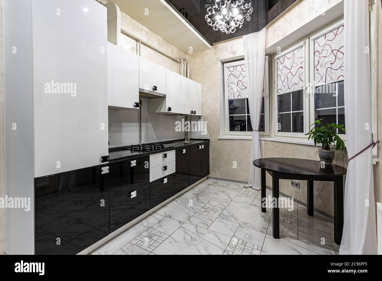 Cozy Modern Kitchen In Small Apartments White Furniture With Black Top And A Wooden Dining Table Interior Design Stock Photo Alamy