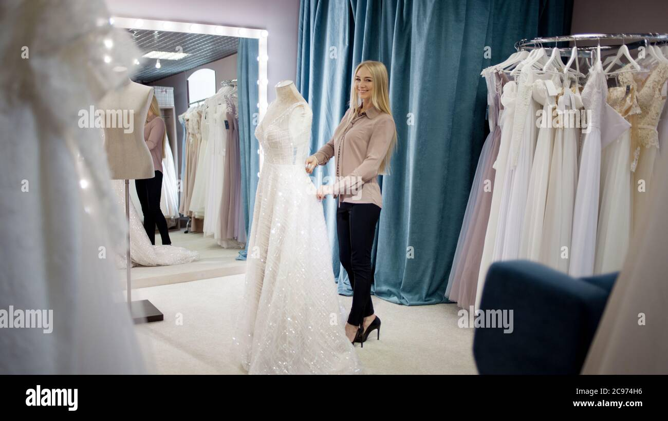 Hostess Of The Wedding Salon Looks At The Wedding Dress Small Business Business Woman With Her Own Store Of Wedding And Evening Dresses Stock Photo Alamy