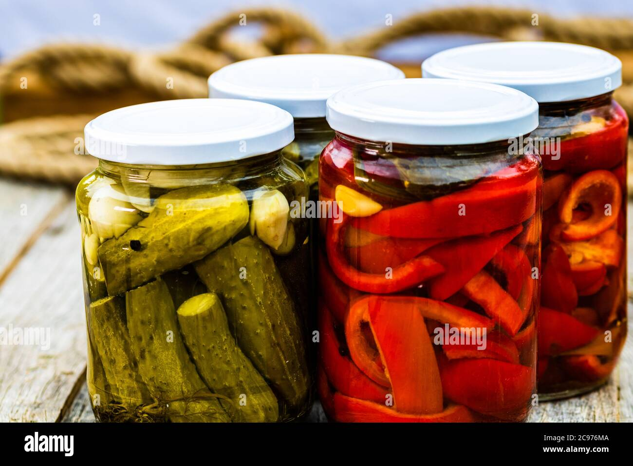 Glass jars with pickled red bell peppers and pickled cucumbers (pickles) isolated. Jars with variety of pickled vegetables. Preserved food concept in Stock Photo