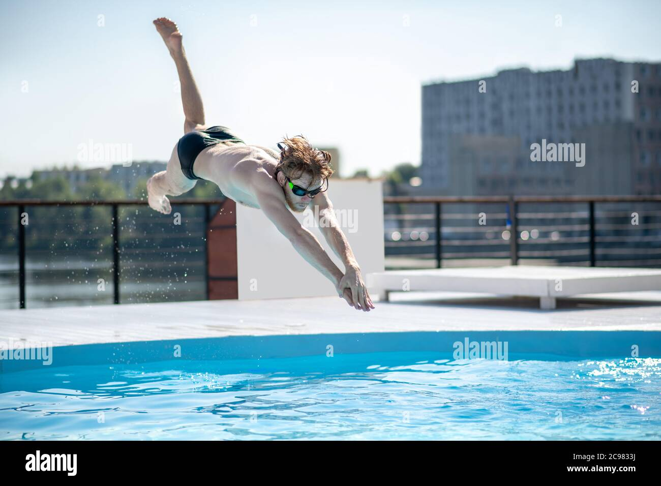 Swimmer at the time of jump in open pool Stock Photo