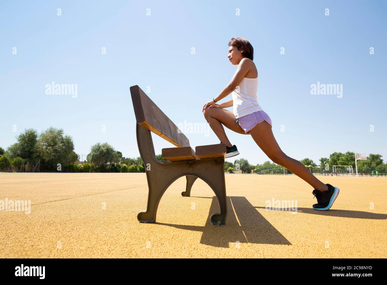 Young woman stretching her muscles on an outdoor bench before doing sport. Space for text. Stock Photo