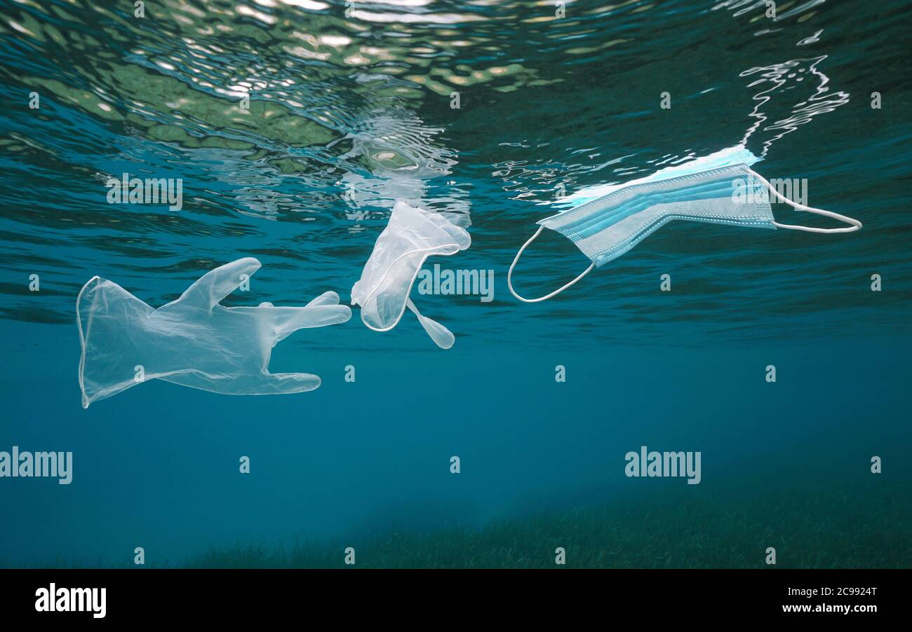 Plastic waste pollution in the sea since coronavirus COVID-19 pandemic, gloves with a face mask floating under water surface Stock Photo