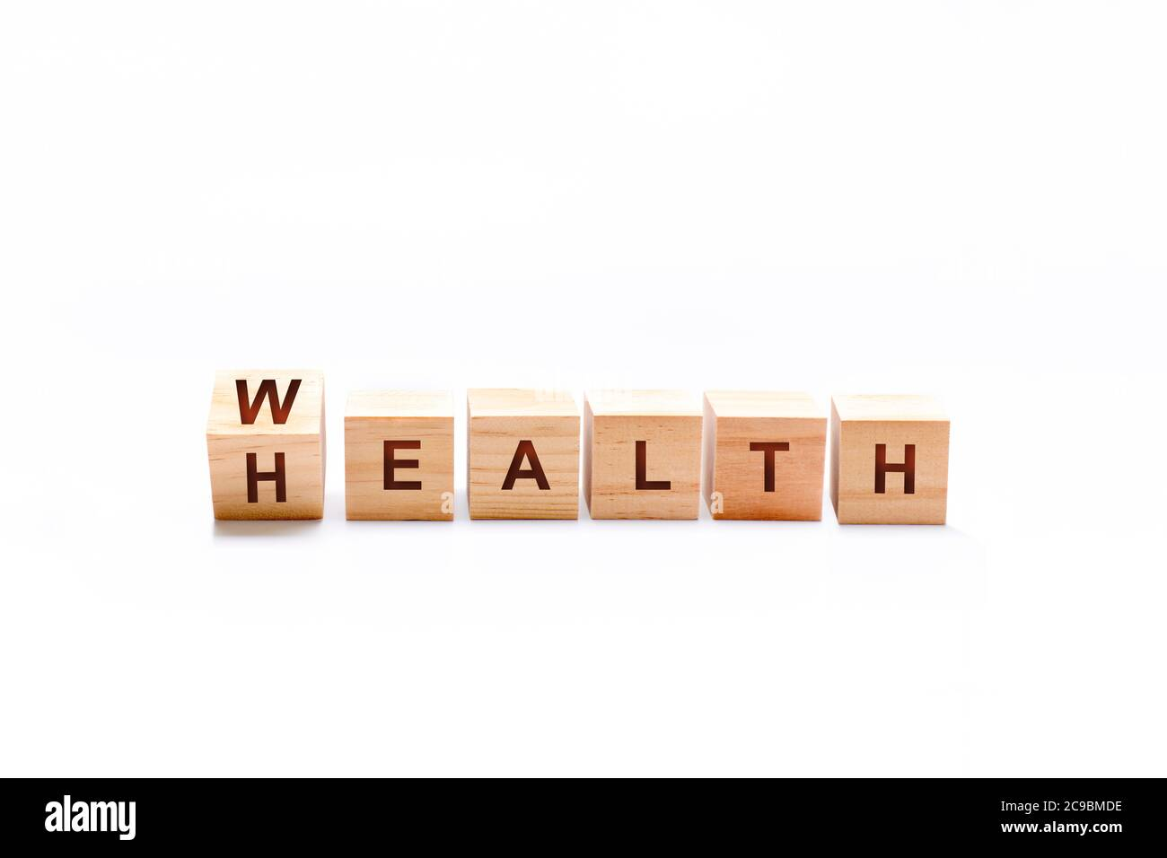 Wooden bucket spinning changing the word HEALTH to WEALTH. Investment in life insurance and healthcare concept Stock Photo