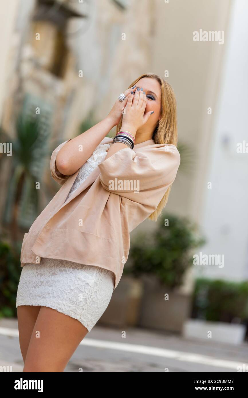 Blonde teengirl very excited excitement surprised big surprise spontaneous candid standing getting back laughing laugh smile smiling happy happiness Stock Photo