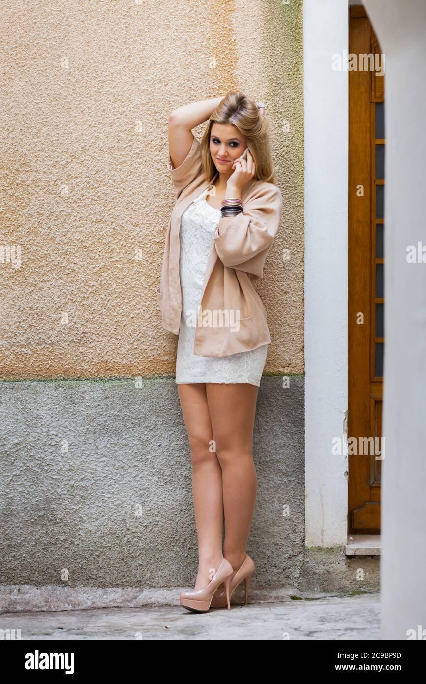 Legs heels blonde teengirl sheer tights talking chatting chat talk on smartphone phone device cellphone serious eyeshot eye eyes contact Stock Photo
