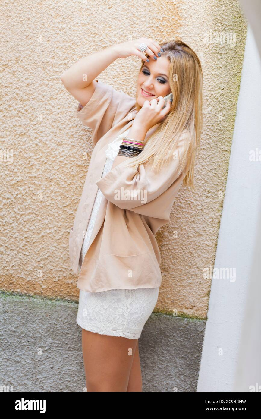 Blonde teengirl talking chatting chat talk on smartphone phone device cellphone slight smile optimistic Stock Photo
