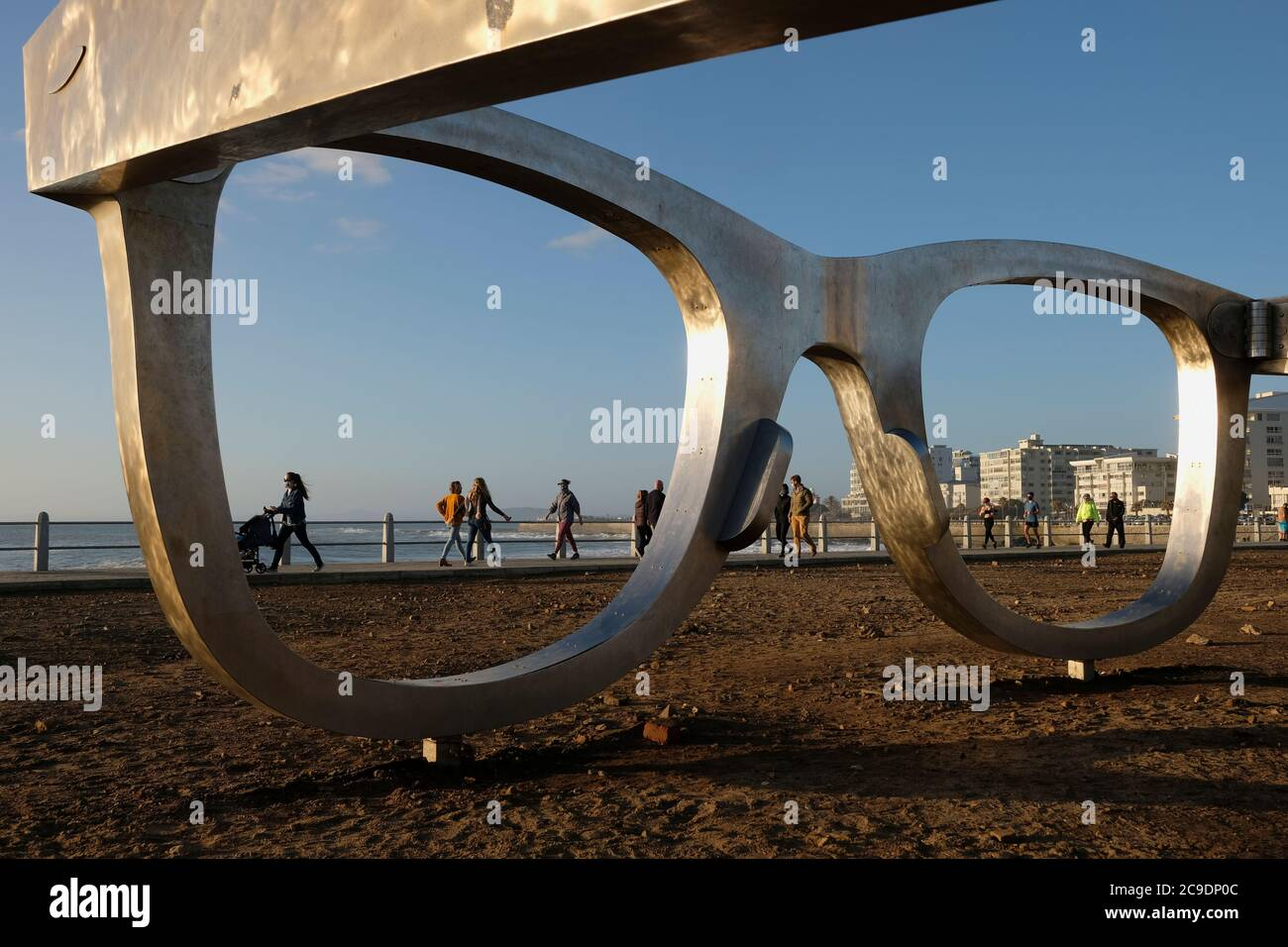 Everyday life on the promenade with Michael Elion's Madiba (Nelson Mandela) inspired public sculpture 'Perceiving Freedom' in Sea Point, Cape Town. Stock Photo