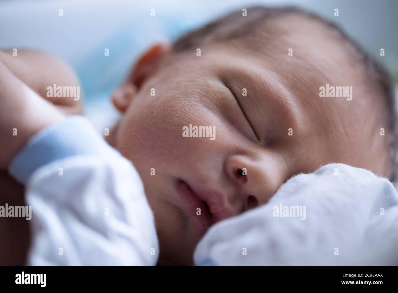 Shirtless newborn baby boy wearing white gloves sleeping Stock Photo