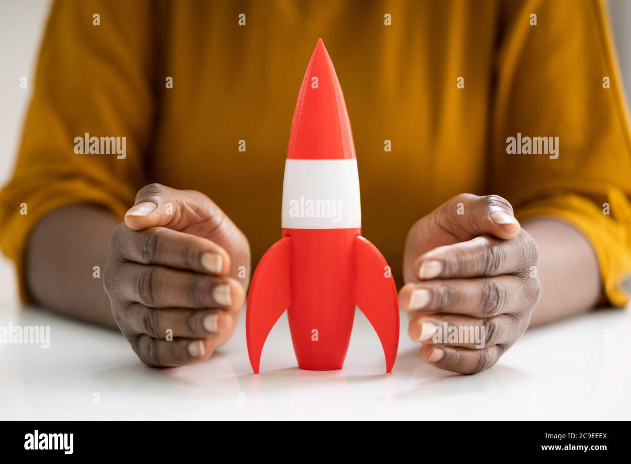 Woman Hands Protecting Red Rocket Launch. Speed Start Stock Photo