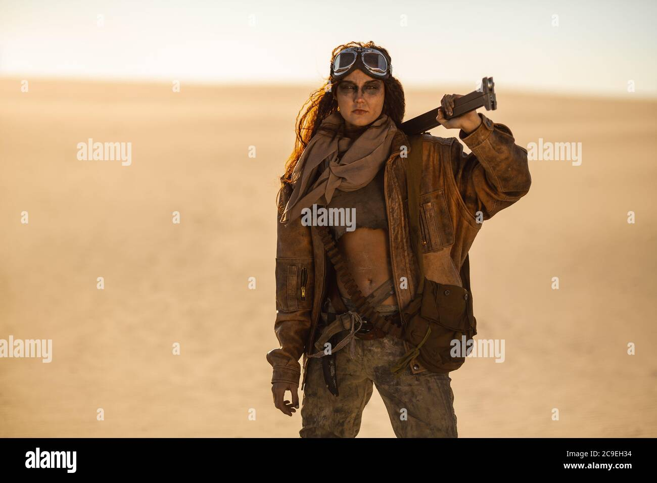 Post-apocalyptic woman with weapon outdoors. Young slim girl warrior in shabby clothes holding sword standing in a confident pose looking at camera . Nuclear post-apocalypse time. Life after doomsday concept. Desert and dead wasteland on the background. Closeup portrait.