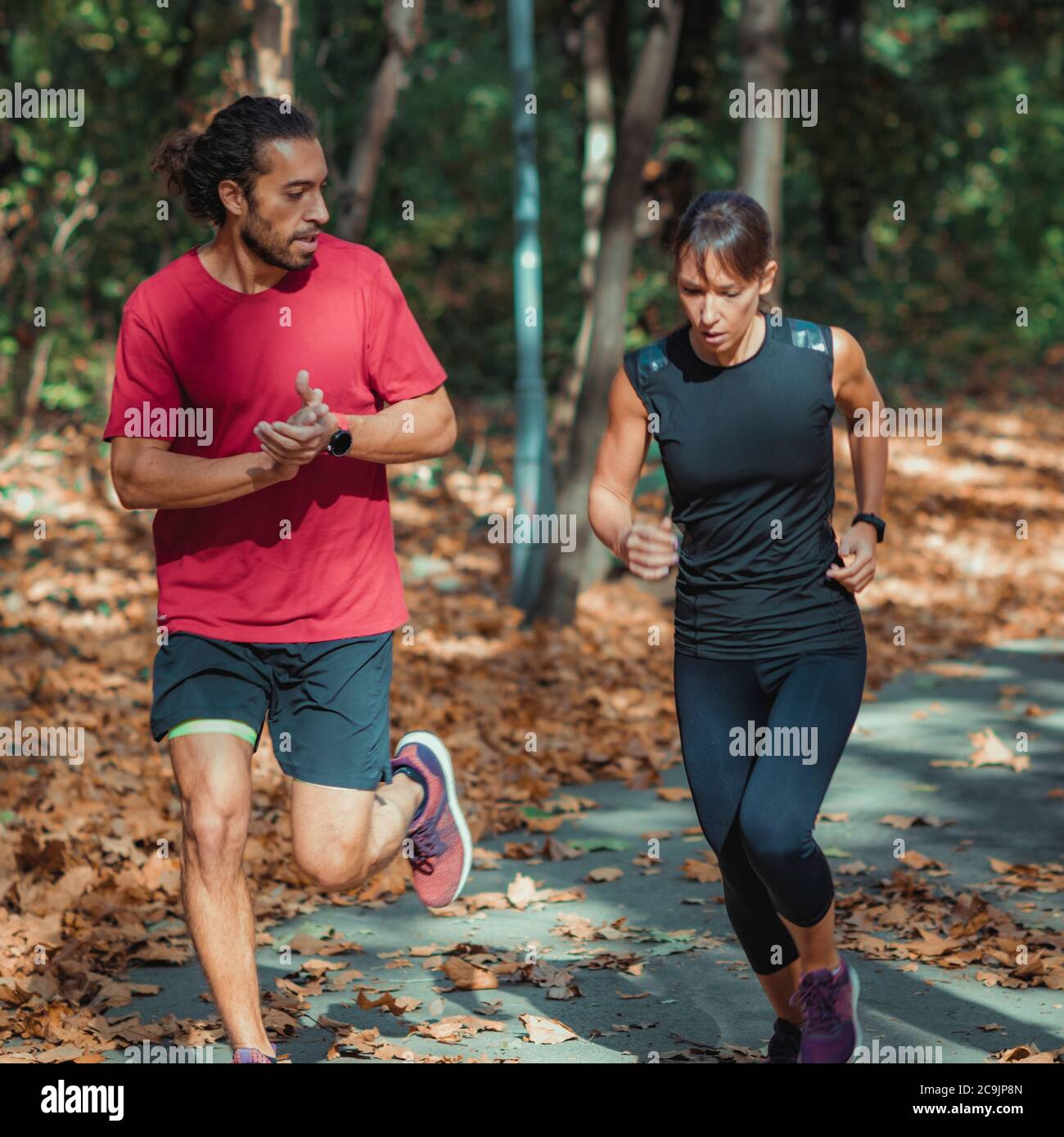 Couple jogging outdoors in park. Stock Photo
